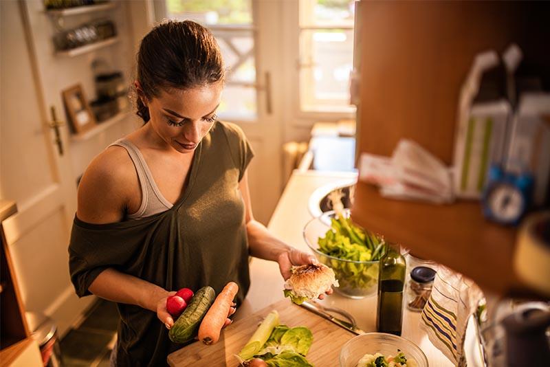 Eine junge Frau die ein Essen mit frischem Gemüse zubereitet.