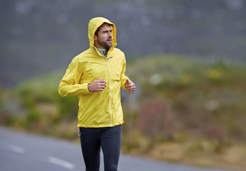 Young man running in bad weather conditions in a yellow jacket.