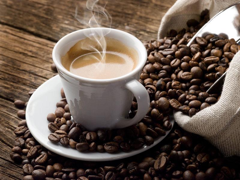 Une tasse de café entourée de grains de café sur une table en bois.