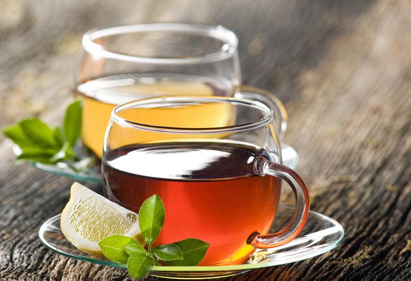 Zwei Tassen Tee auf einem Holztisch.