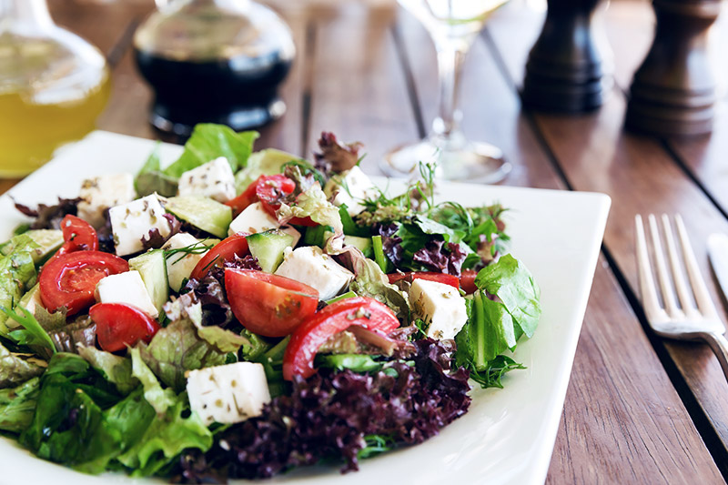 Gesunder Salat mit Ziegenkaese auf einem Teller.