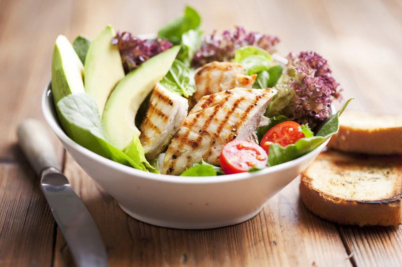 Eine Schüssel grüner Salat mit Putenstreifen und Avocado