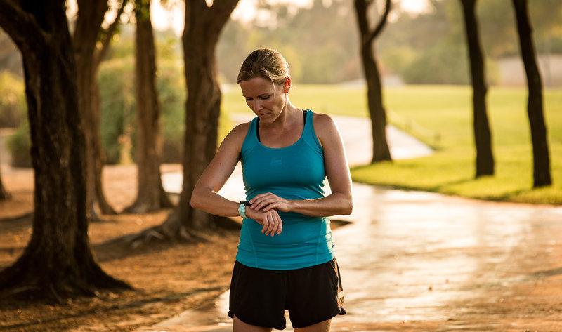 Eine Frau checkt ihre Garmin Uhr nach dem Lauf im Park