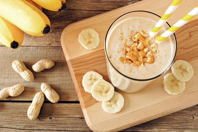 Ein Glas Erdnussbutter-Bananen-Shake auf einer Holzplatte