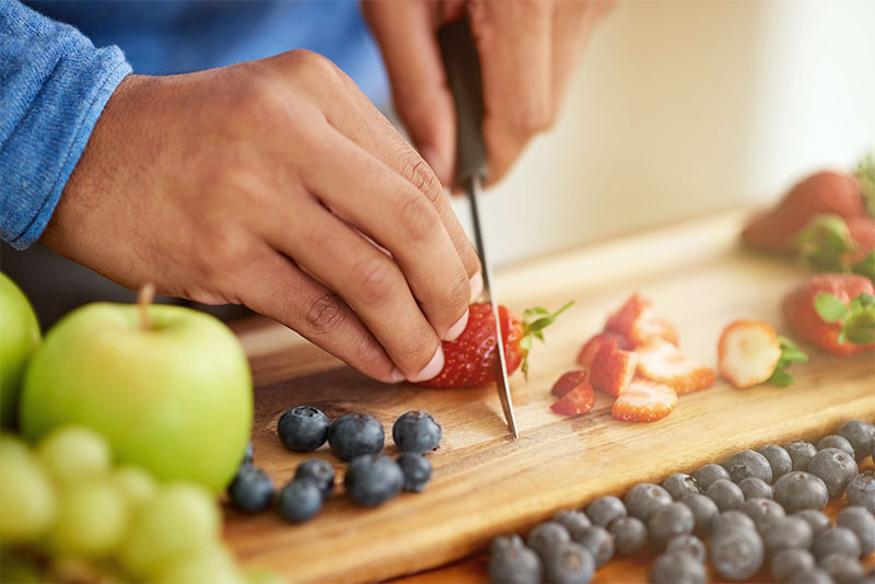 Someone cutting strawberries on a wooden plate