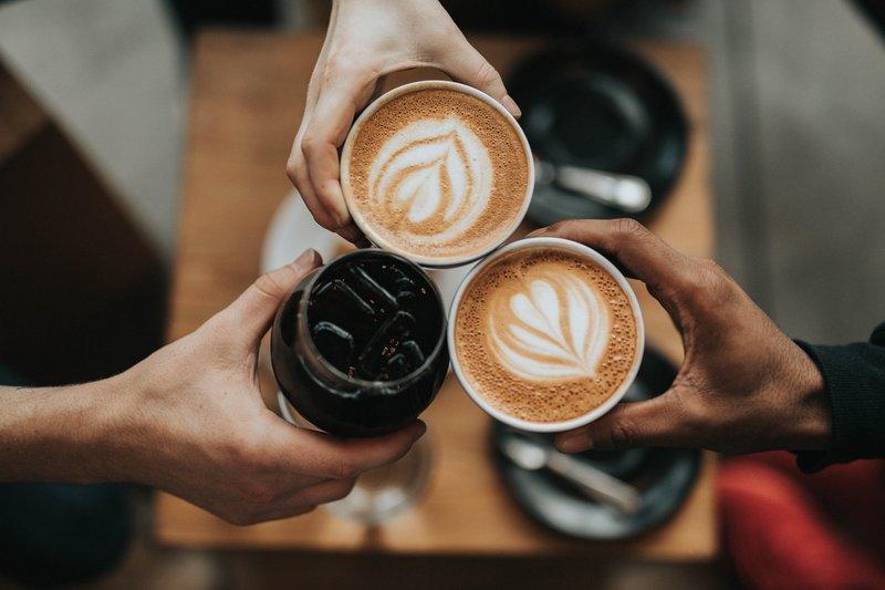Drei Personen stoßen mit ihrem Kaffee an