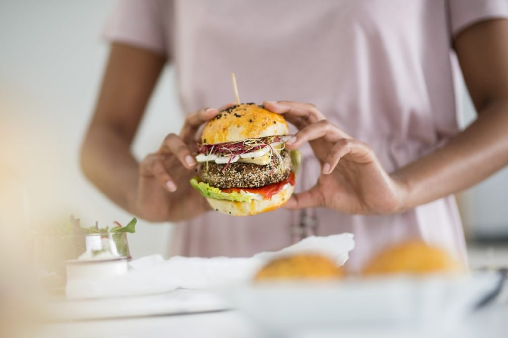 someone holding a burger