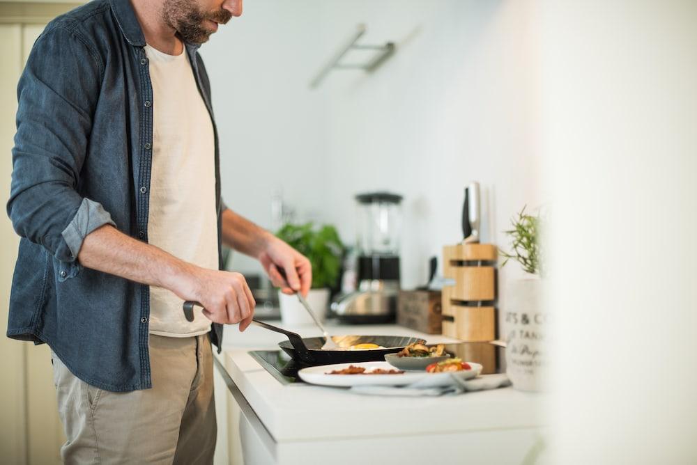 Homem preparando ovos mexidos