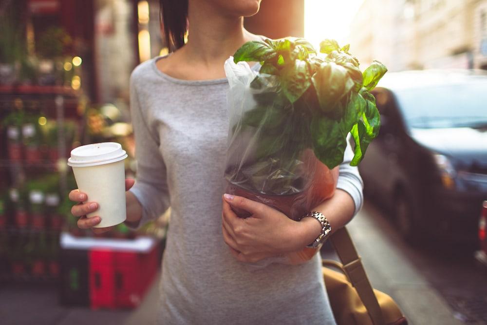 une femme porte ses courses et un gobelet en plastique avec du café