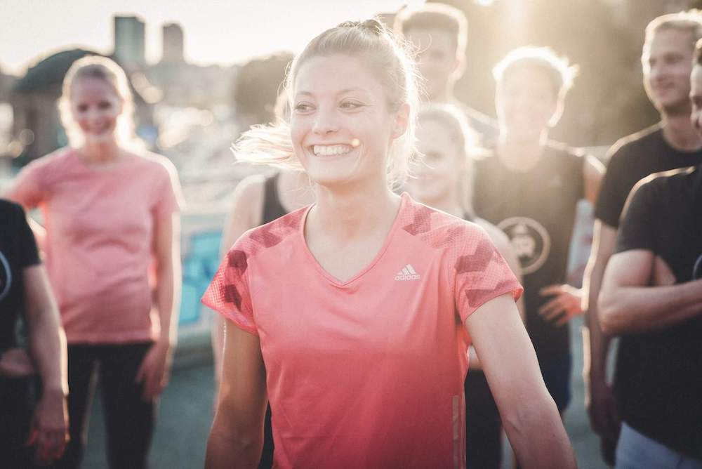 une femme heureuse s'entraîne avec un groupe de coureurs