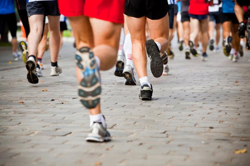 Nahaufnahme von den Beinen einer Gruppe von Marathonlaeufern.