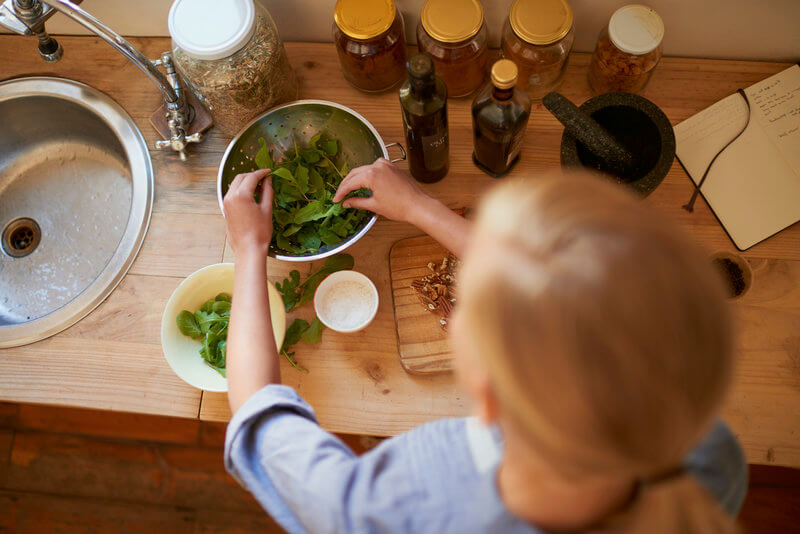 Woman preparing a fresh green salad.