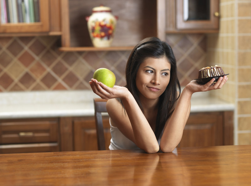 Girl holding an apple and a cake in her hands.