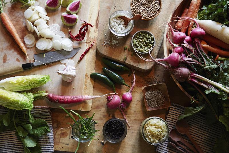 Photo de légumes et de graines sur une table en bois.