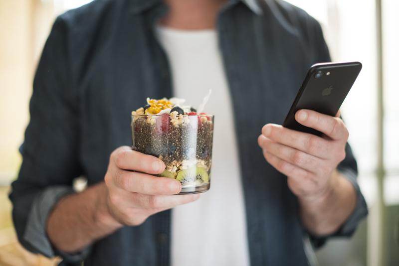Ein Mann hält ein Glas Chiapudding in einer Hand und sein Smartphone in der anderen