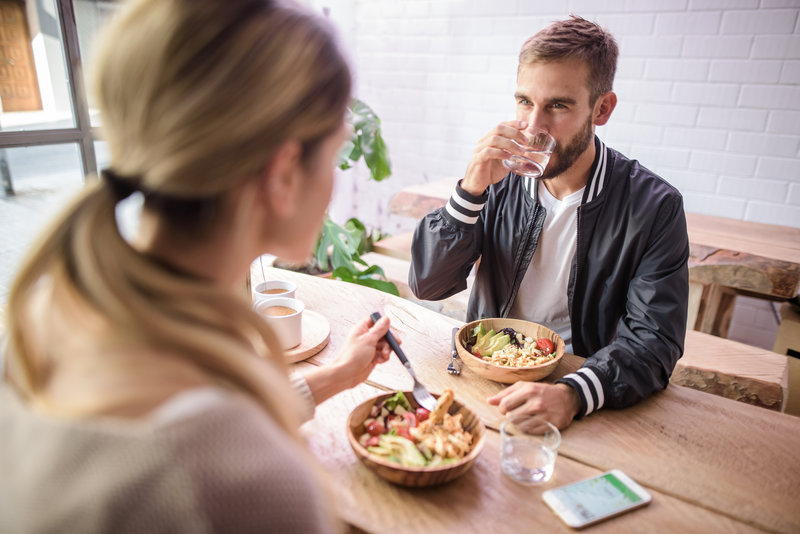 A man and a woman are having lunch. The man is drinking water from a glass.