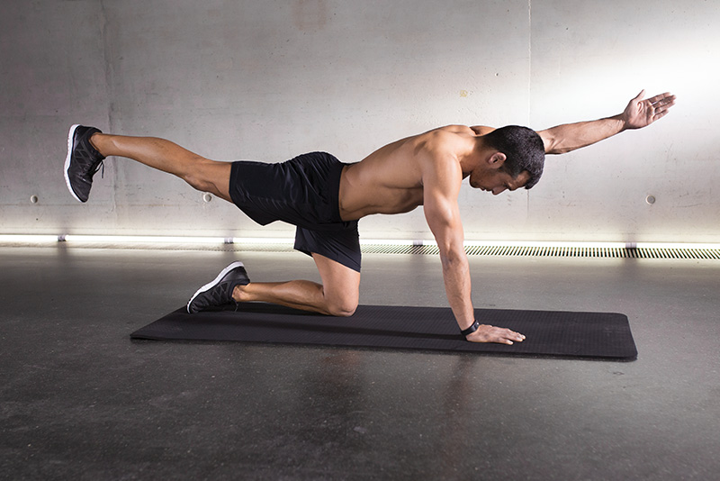 A shirtless man doing bodyweight training inside