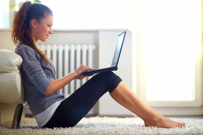 young woman sitting on the floor in the livingroom with a laptop on her knees.