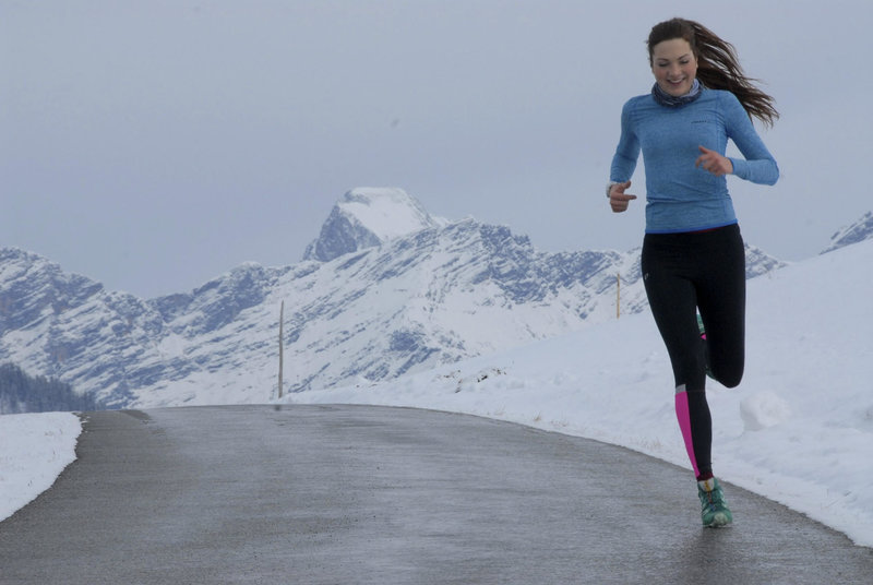 Young woman running on the road in winter.
