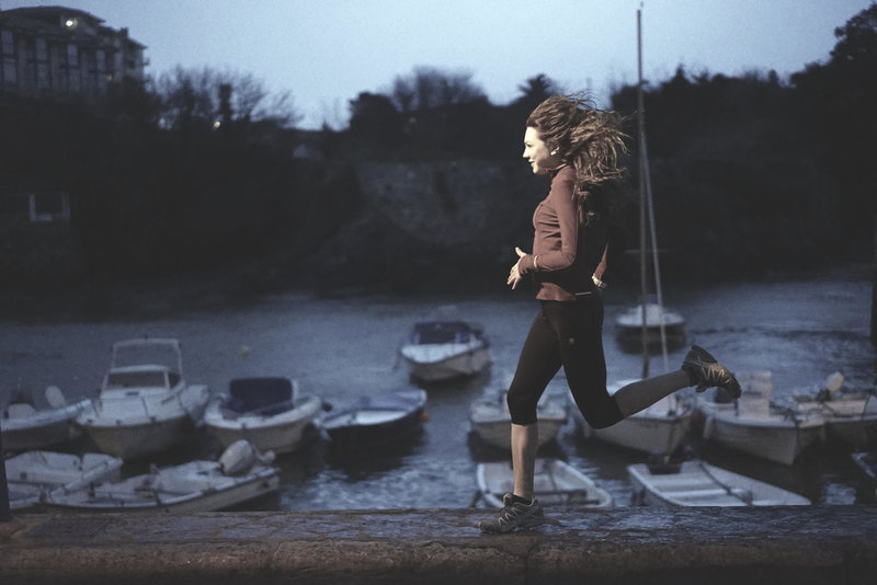 Young woman running along the harbor.