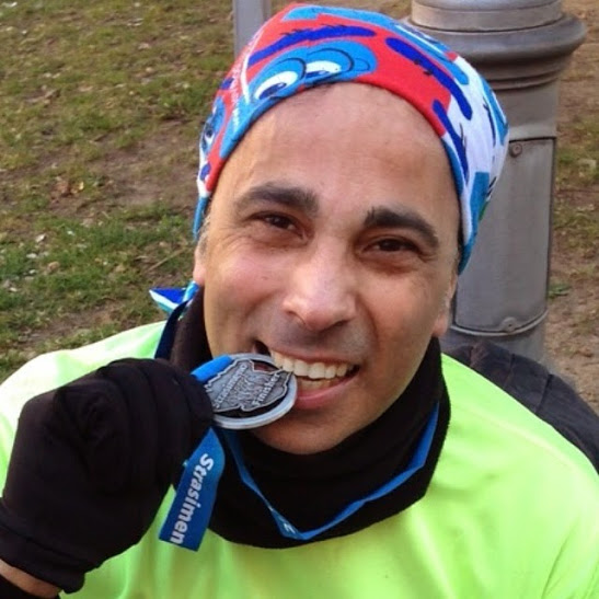 Runner is posing with his medal.
