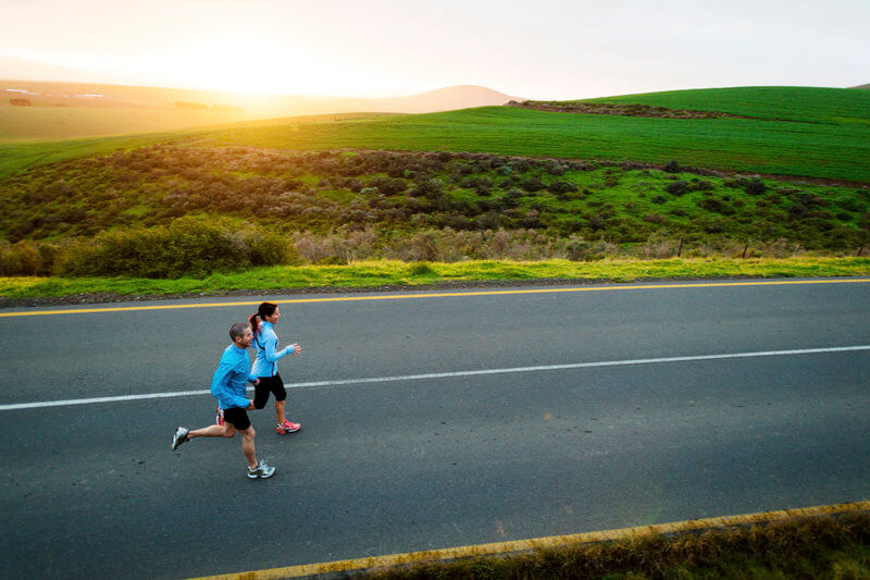 Couple is running into the sunrise.