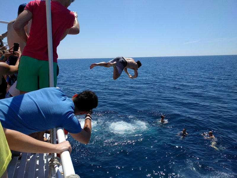 Boy is jumping from a boat into the sea.
