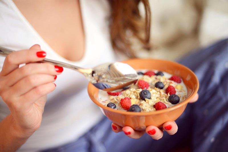 Junge Frau fruestueckt ein Muesli mit frischen Fruechten.