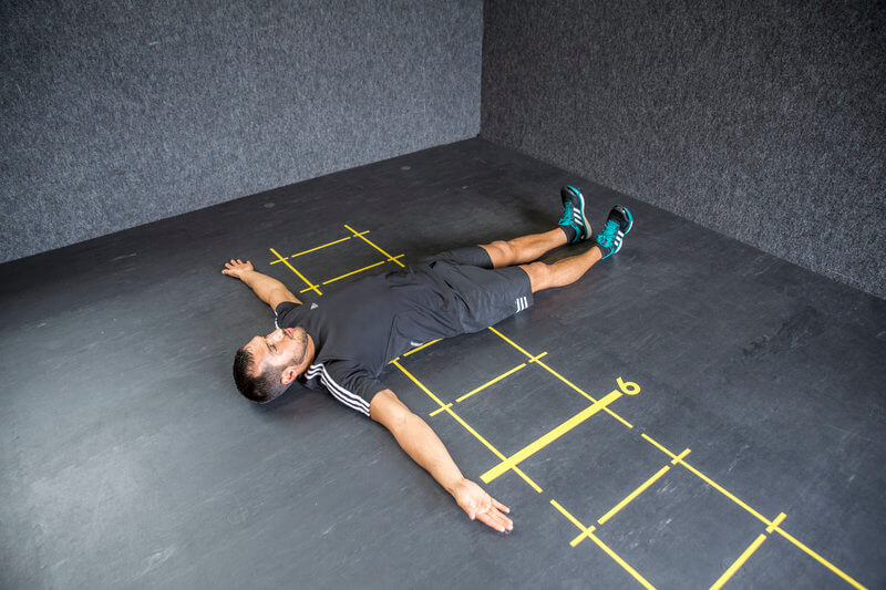 Young man who is doing the Scorpion 2 exercise.
