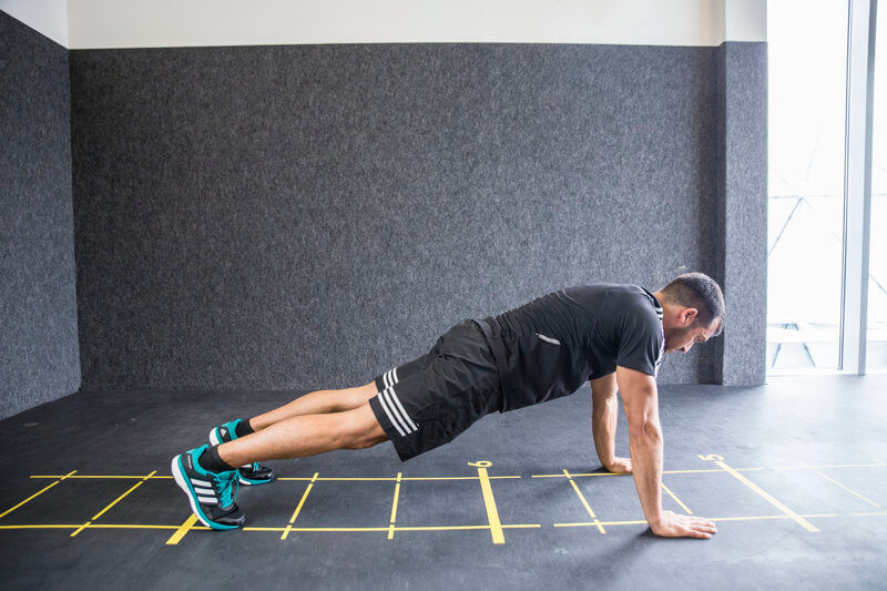 Young man who is doing an Inchworm exercise.