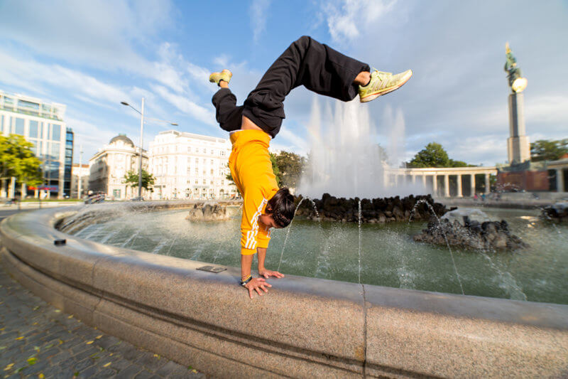 Pam Forster who is going a cartwheel at the pavement of a well.