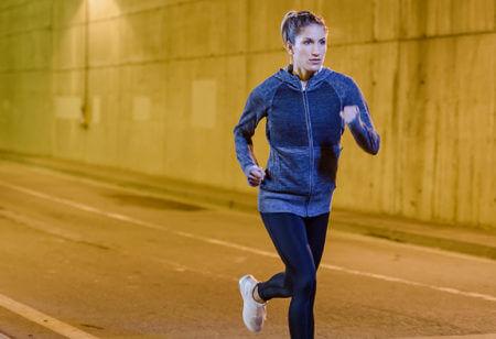 Eine Frau läuft nachts in einem Tunnel