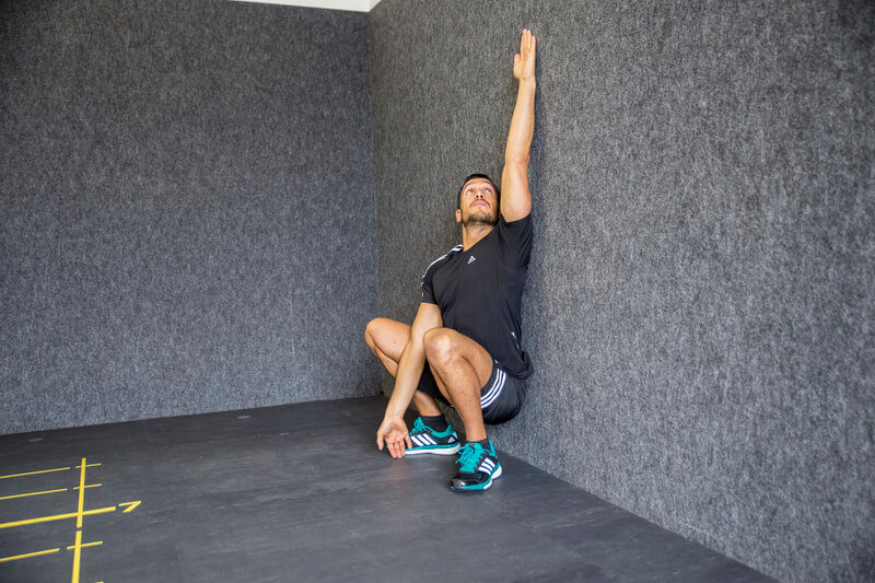 Young man is doing a Wall Squat.