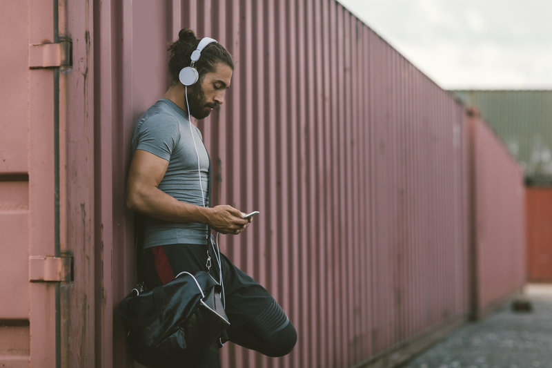 Athletic Man Resting After Running. He is running in the city every day, preparing himself for marathon race. Standing, listening music and holding his smart phone. Also texting or typing on his smart phone. Wearing gym bag.