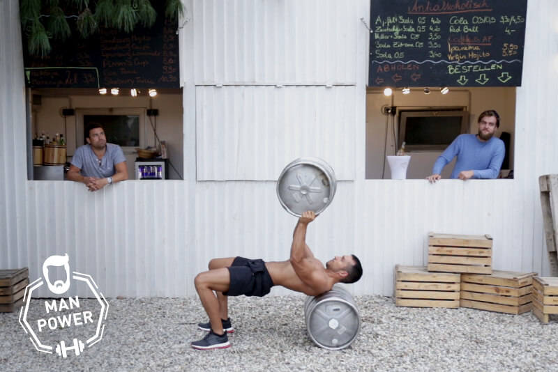 Young fit man doing bench press with a beer barrel.