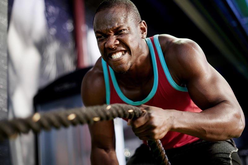 Jeune homme musclé entrain d'effectuer un entraînement intense à la salle de fitness.