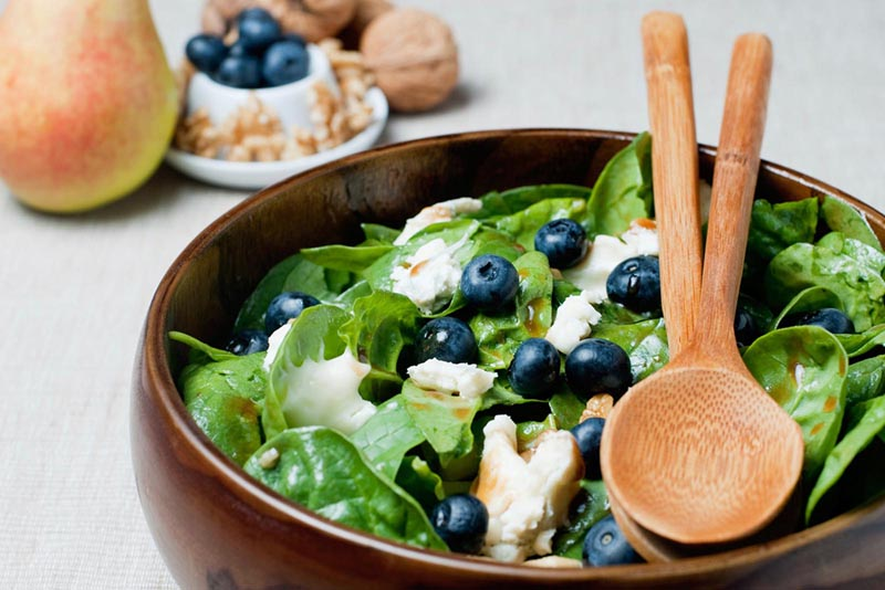 Bowl with baby spinach, blueberries and goat cheese
