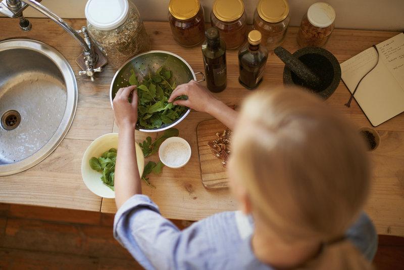 Junge Frau bereitet einen gesunden Salat in der kueche.