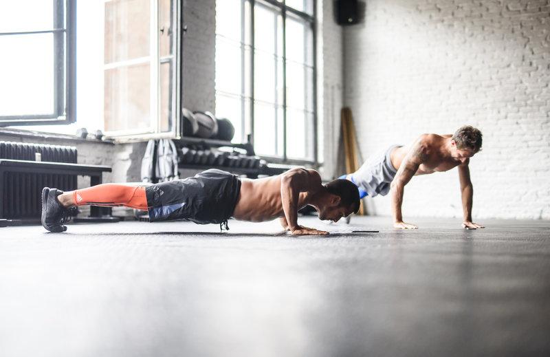 Zwei Freunde mit freiem Oberkoerper beim gemeinsamen Workout.
