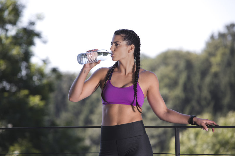 Athletic woman drinking out of her water bottle.