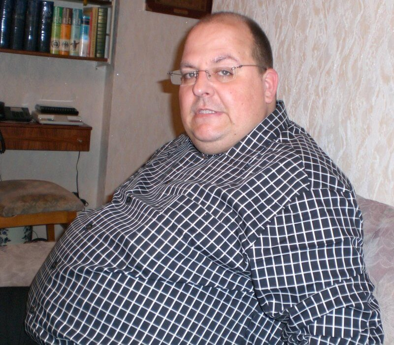 An overweight man looking unhappy