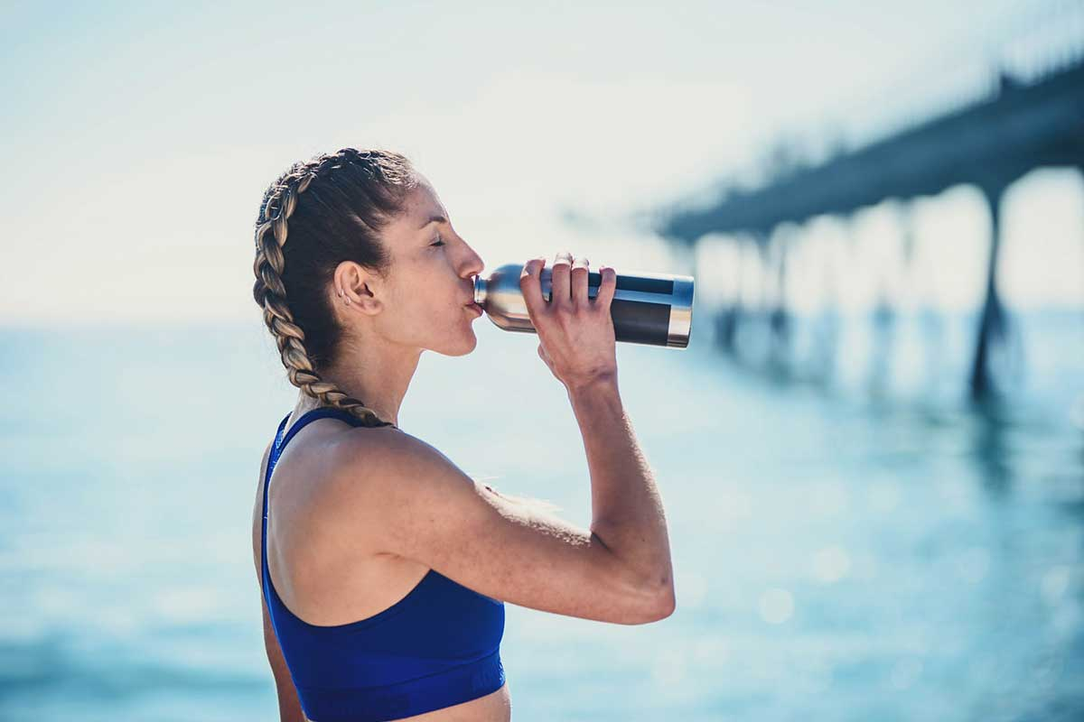 a young lady at the beach is drinking from a sustainable water bottle