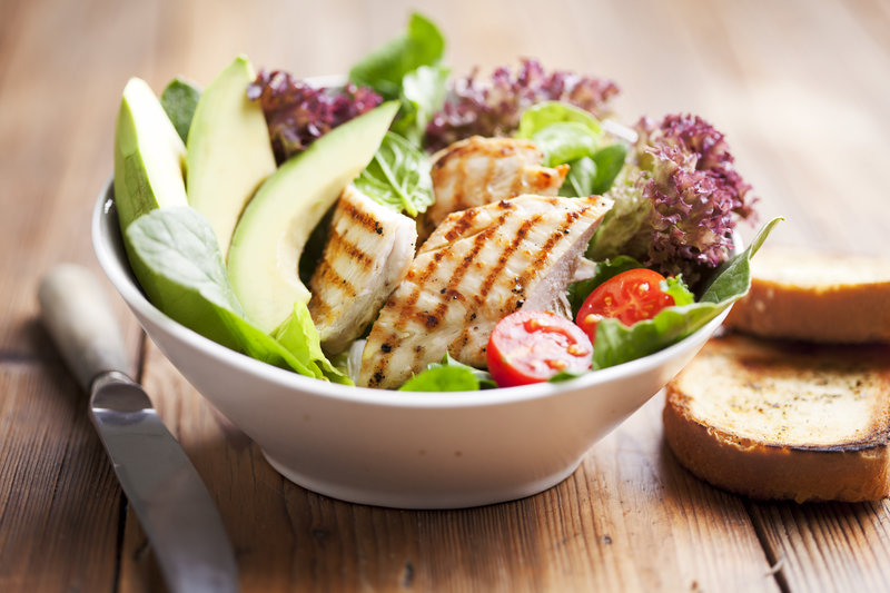 A salad bowl with turkey strips and avocado