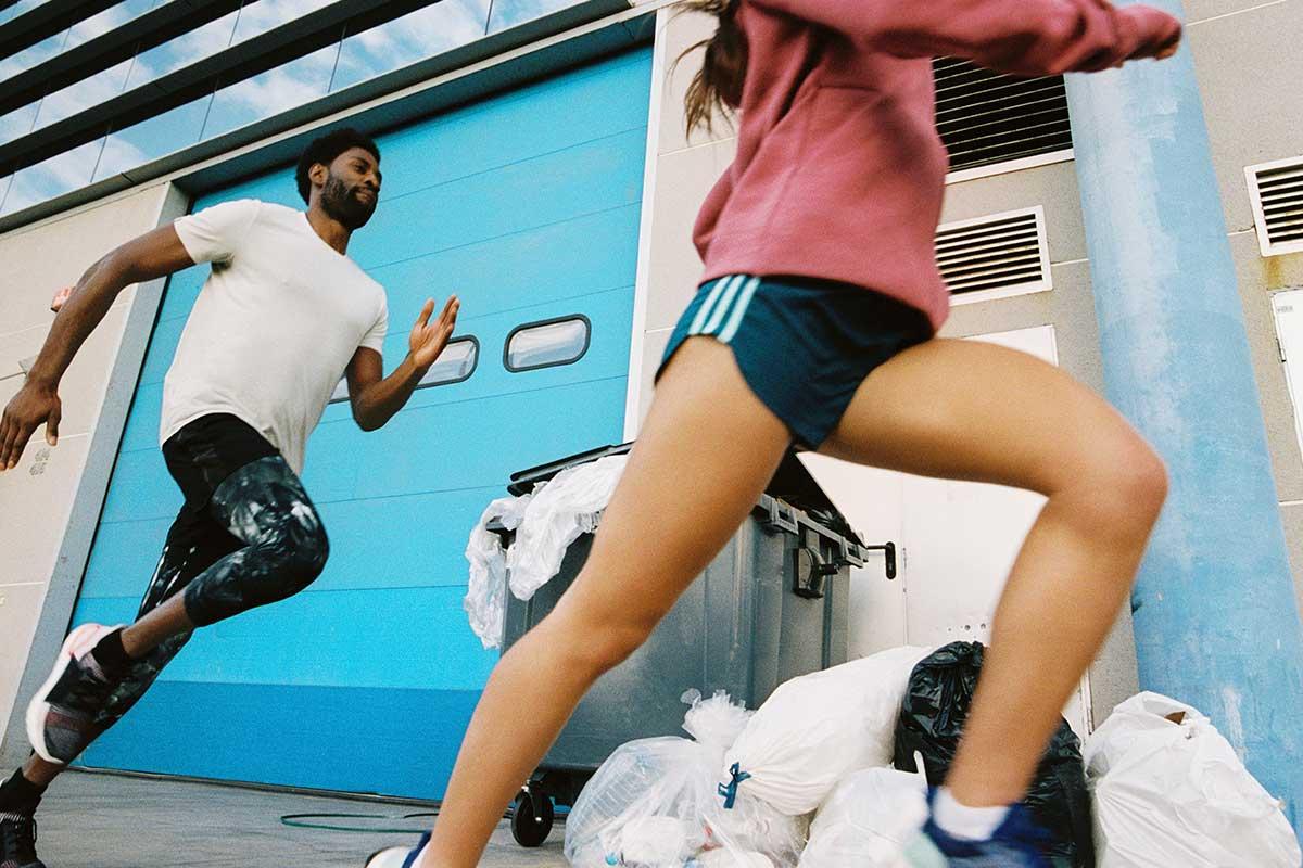 Zwei junge Menschen laufen in einer Stadt an einem Müllberg aus Plastik vorbei