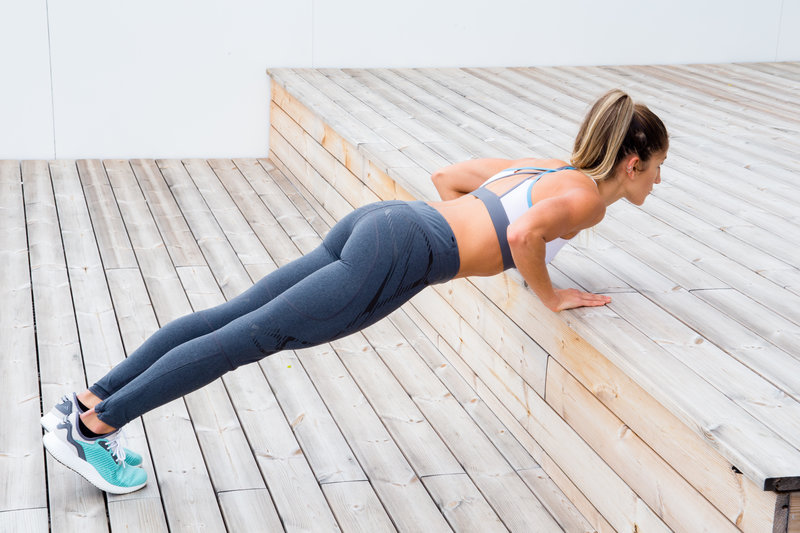 Woman is doing inclined push-ups