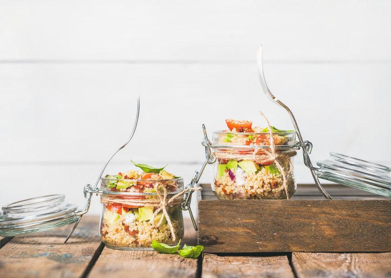 Selbstgemachter Quinoasalat in Glasgefäßen auf einem Holztisch