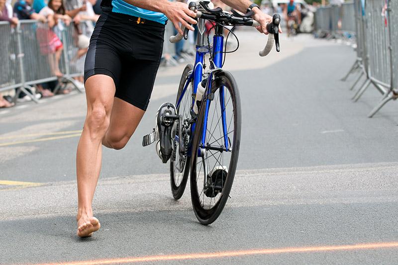 Jemand läuft während eines Triathlons mit dem Fahrrad