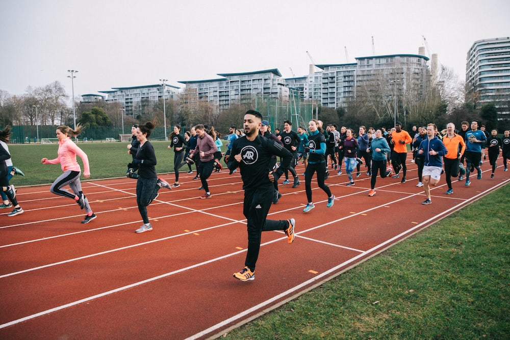 Young people running together on track
