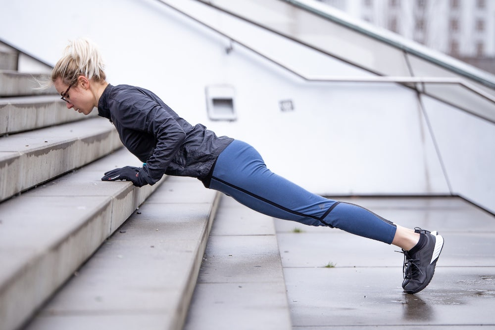 Woman doing push up on stairs