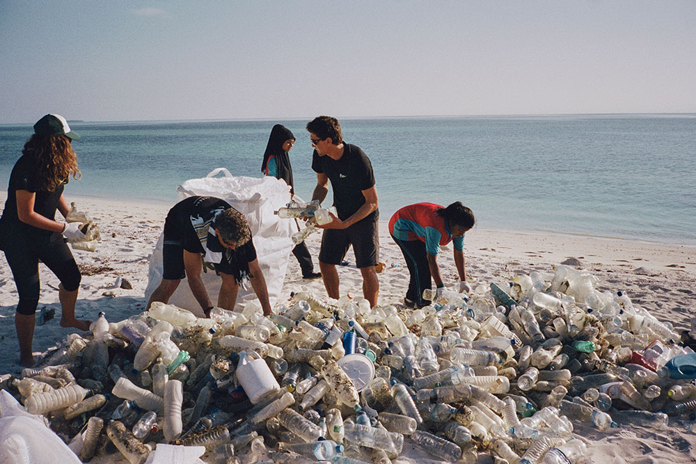 "A group of young people collect plastic trash to contribute to the project ""Parley Ocean School"" by adidas"